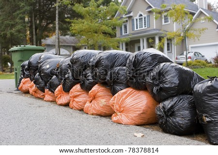 Many orange and green garbage bags at curb
