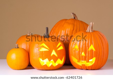Many orange halloween pumpkins and Jack O Lanterns.