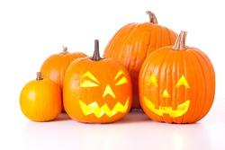 Many orange halloween pumpkins and Jack O Lanterns isolated on white background.