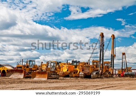 Many orange machines standing on the ground