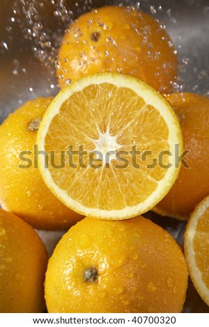 Many oranges washed in the sink in a kitchen.
