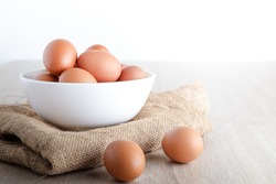 Many organic chicken eggs are placed in a white bowl on a wooden floor. Food concepts that are beneficial to the body provide high energy. copy space