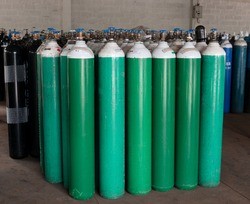 Many oxygen cylinders and argon cylinders with compressed gas secured in the Gas factory warehouse. Green Oxygen tanks for hospital. Black Oxygen tanks for industry. Blue argon tanks for industry.