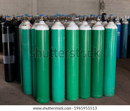 Many oxygen cylinders and argon cylinders with compressed gas secured in the Gas factory warehouse. Green Oxygen tanks for hospital. Black Oxygen tanks for industry. Blue argon tanks for industry. Stok fotoğraf ©