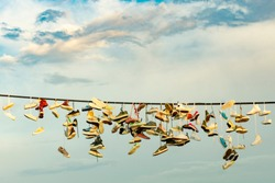 many pairs of shoes suspended on a rope against a blue sky with clouds