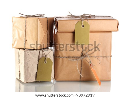 Many parcels wrapped in brown paper tied with twine and with blank labels isolated on white