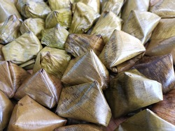 Many pastries wrapped in banana leaves.Candles dessert are popular candies used in merit-making events.  Especially paying respect to ancestors Chinese New Year festival