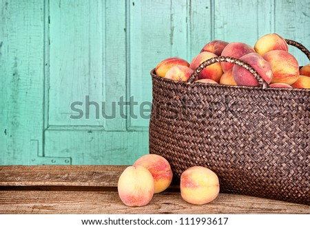 Many peaches in a basket with antique panel background