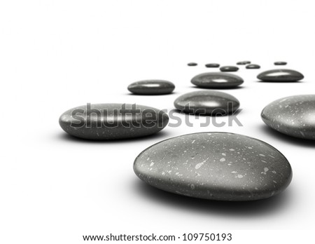 many pebbles on a white floor, stones are black with grey dots, there is a blur effect on the background, the front stone is clear