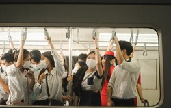 Many people on the train wear anti-virus masks and travel during rush hours. business asian man on sky train.