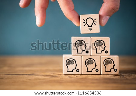 many people together having an idea symbolized by icons on cubes