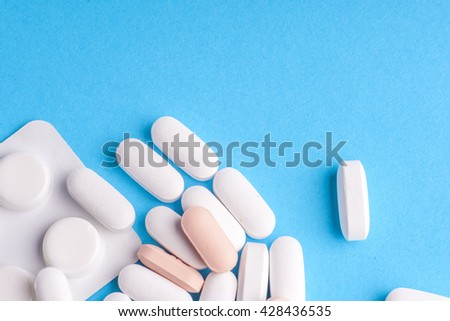 Many pills and tablets isolated on light blue background. Pharmaceutical medicament, cure in container for health. Antibiotic, painkiller closeup. Copy space for text. #428436535