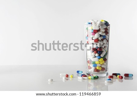many pills in a glass tumbler, shot on a white background