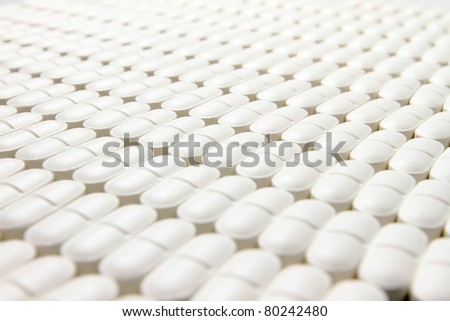 Many pills neatly stored on a flat surface, focused to center