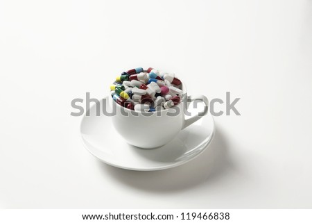 many pills shot in a cup and saucer on a white background