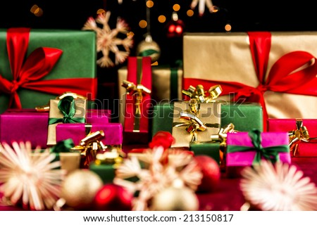 Many plain Christmas presents piled up on a red cloth. All with unicolored bows in red, green and gold. Narrow depth of field resulting in bokeh. Blurred ornaments and stars in front and back. #213150817