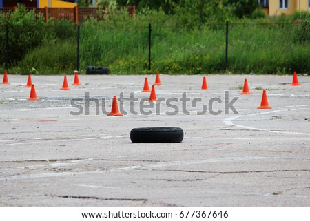 many plastic signaling traffic cones and Rubber tires from wheels are on site for training where drivers learn to ride on cars. #677367646