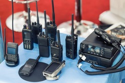 Many portable radio transceivers on table at technology exhibition. Different walkie-talkie radio set. Communication devices choice for military and civil use
