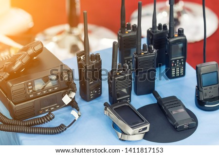 Many portable radio transceivers on table at technology exhibition. Different walkie-talkie radio set. Communication devices choice for military and civil use #1411817153
