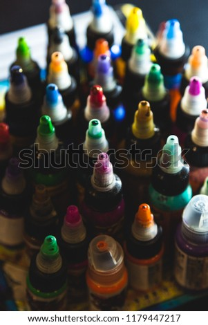 many professional bottles with colored ink for tattoos. tattoo parlor #1179447217