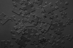 Many puzzles are randomly scattered on the plane. Photo of black puzzles on a black background, business background