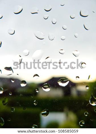 many rain drops during bad weather on a window pane. rainy weather
