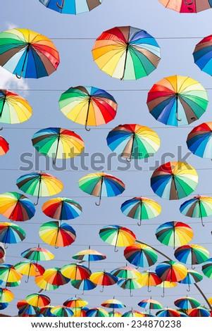 Many rainbow umbrellas strung across the street