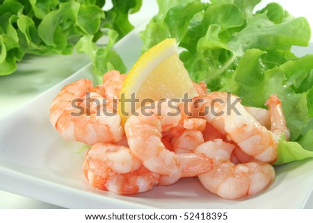 many raw shrimp with lemon on lettuce leaves on a plate