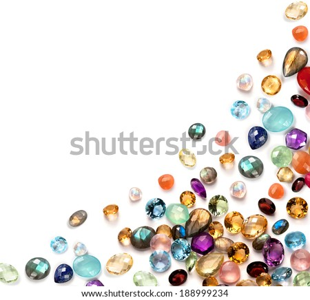 Many real colorful polished gemstones on the white background. Composition with empty space in the left top corner.