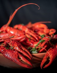 Many red boiled fresh crayfish/crawfish in a bowl with green parsley, close-up seafood cheliped pincer claw
