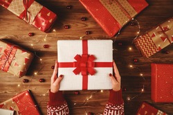many red Christmas gifts with hands and garlands of lights on wooden background