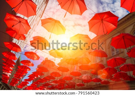 Many red umbrellas hanging from a roof