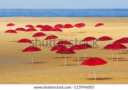 Many red umbrellas stuck in the sand of a beach in a summer morning