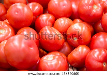 many ripe tomatoes. laid out on the counter on the market for sale.