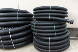 Many rolled colis of new black corrugated goffred plastic electric plumbing drainage pipe prepared for installation near building construction site. Drain sewage tube hose conduit pipeline