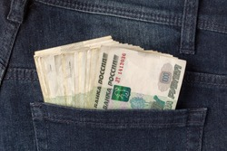 Many roubles sticking out of the back pocket of jeans shot closeup.
