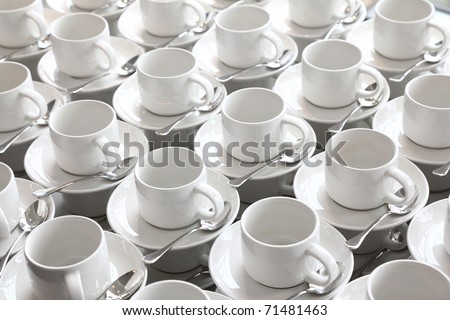 many rows of pure white cup and saucer with teaspoon, reflection on table