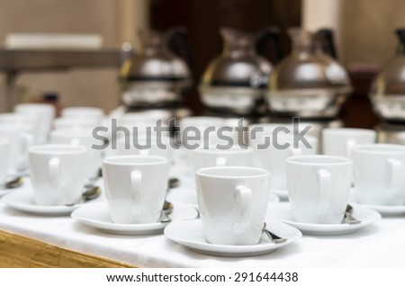 Many rows of white coffee cup with saucer and teaspoon on table and coffee maker background #291644438