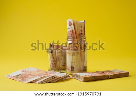 Many russian bank notes in a glass jar isolated on yellow background. Save money in rainy day Foto stock ©