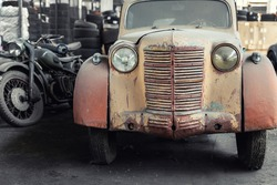 Many rusty abandoned forgotten antique oldtimer old car and motorcycles at junkyard factory storage warehouse indoors. Classic vintage retro vehicles detail garage workshop restore renovation station