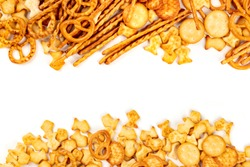Many salt crackers, sticks, pretzels, and fishes, shot from aboveon a white background with a place for text. Party snacks mix, forming a frame with copy space