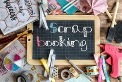 many scrapbooking accessories and a school slate at the center with the word scrapbooking