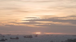 Many ships in sea at port at sunset. Action. Sea coastal port with variety of different ships at sunset. Tankers, cargo ships and vessels sail off coast on background horizon at sunset
