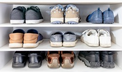 Many shoes of man and woman in different fashion style put in 3 storeys white shoe rack. Everyday footwear collection use for variety seasons and lifestyle (sport, casual and leather business shoes).