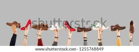 many shoes on arm raised hands
