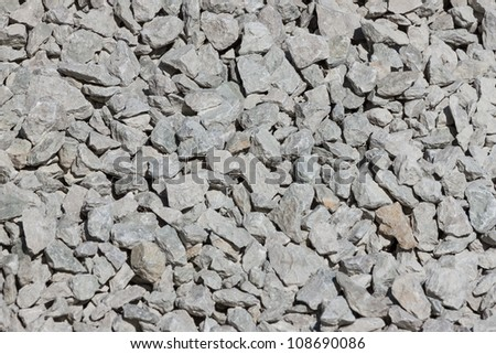 Many small grayish stones used in road construction