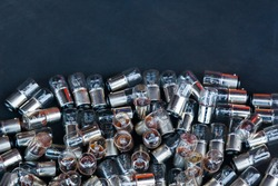 Many small incandescent bulbs lie in a heap on a black background, close-up.
