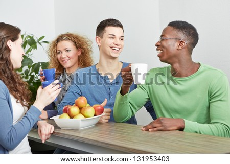 Many smiling colleagues drinking coffee in break room