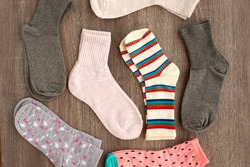 Many socks. Socks on a wooden background. Knitted socks for the cold season. Warm clothes for autumn, winter and spring. View from above. Warm clothes on a wooden background.