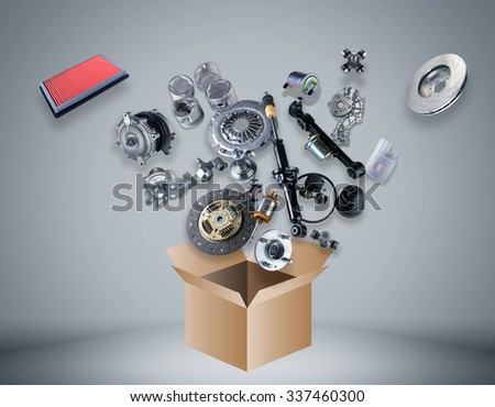 Many spare parts flying out of the box gray background. Isolated auto spare parts on gray background. Auto spare parts for passenger car, OEM. Isolated absorber, gasket, filters, parts for chassis. #337460300